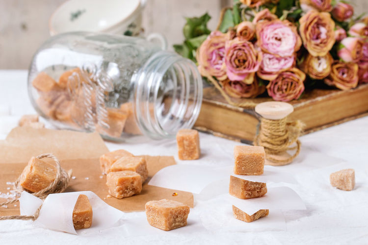 Fudge candy and caramel on baking paper and in glass jar, served over white tablecloth with bouquet of dry pink roses and thread for gift making. See series Baking Paper Beige Brown Butterscotch Candy Caramel Confection Confectionery Creamy Cubes Dessert Dry Roses Food Food And Drink Fudge Glass Jar Homemade Food Mason Jar Sugar Sweet Food Table Tablecloth Tea Time Toffee White