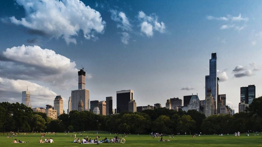 People At Central Park By Buildings Against Sky