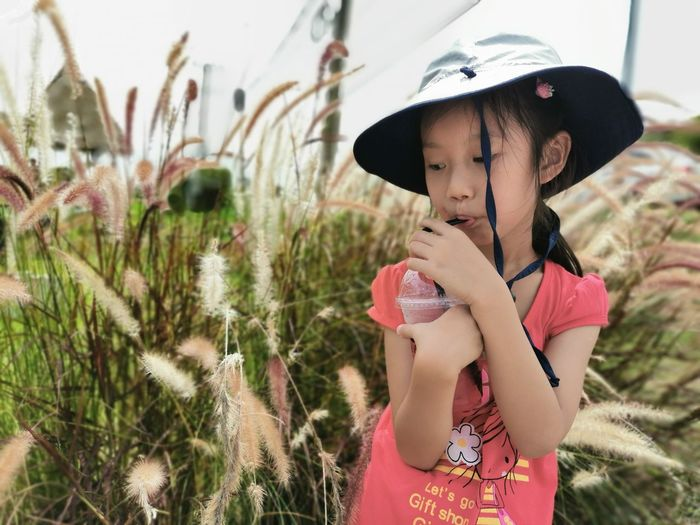 Close-up of girl having drink while standing by plants