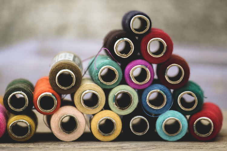Stack of multi colored thread spools on table