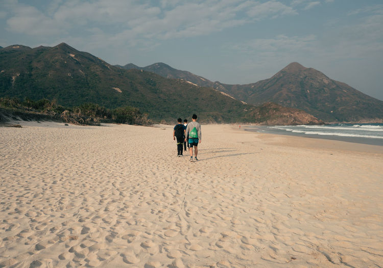 Mountain Land Sky Real People Beauty In Nature Beach Scenics - Nature Sand Rear View Men Nature Leisure Activity Cloud - Sky Togetherness Two People People Full Length Lifestyles Tranquility Non-urban Scene Mountain Range Outdoors