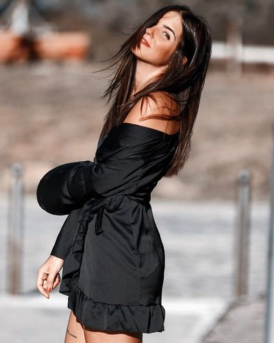 Side view portrait of beautiful woman wearing black dress standing outdoors
