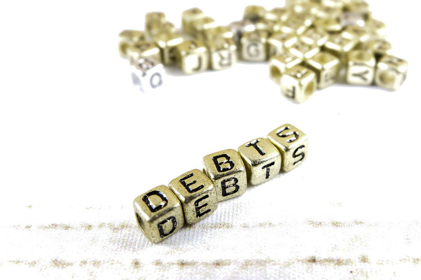DEBT CONCEPT WITH GOLD DICE ON A WOODEN TABLE Arts Culture And Entertainment Capital Letter Close-up Communication Copy Space Credit Card Debt Crisis Focus On Foreground High Angle View Indoors  Jewelry Letter Metal No People Number Still Life Studio Shot Table Text Toy Western Script White Background