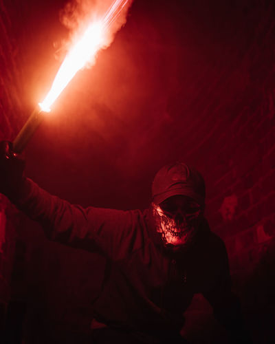 Portrait of man holding blowtorch at night