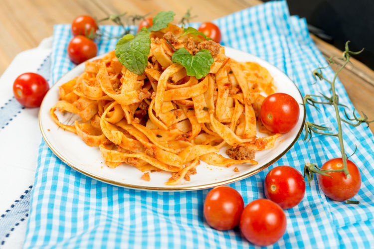 Close-up of fresh spaghetti served in plate and ketchup on paper