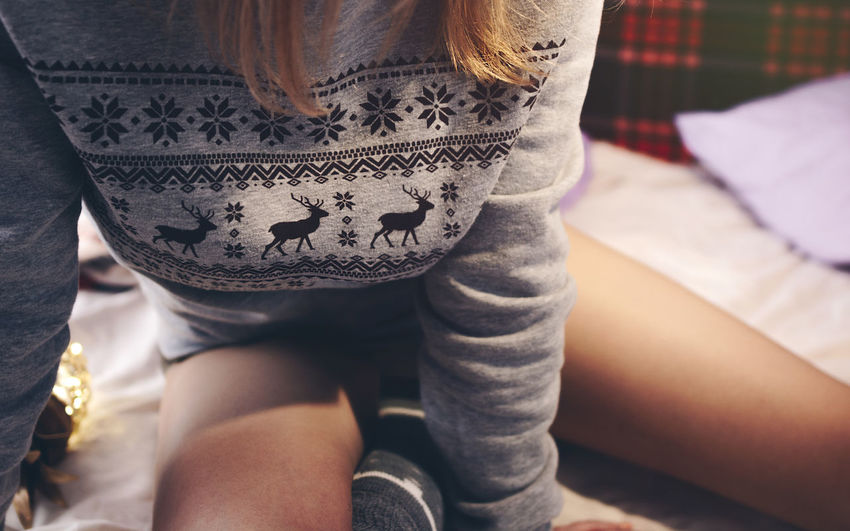 Girl sitting on the bed in the Christmas sweater with a reindeer ornament Women Lifestyles Indoors  Young Women Sitting Bed Young Adult Midsection Girl Christmas Christmas Ornament Bed Legs Socks Kneesocks Ornament Holiday Sitting Redhead Sweater 2018 In One Photograph International Women's Day 2019