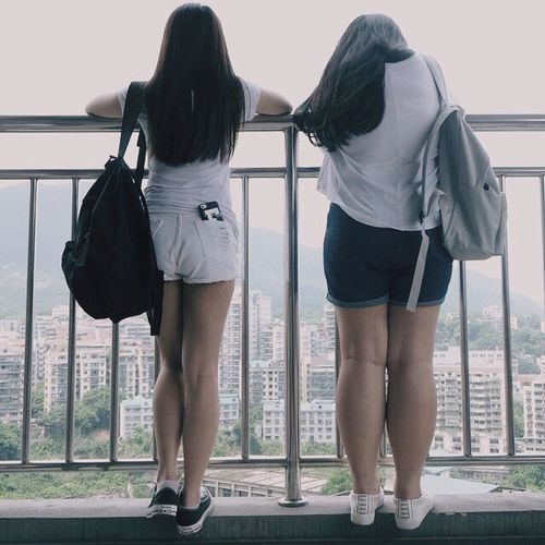 Rear view of women standing on railing