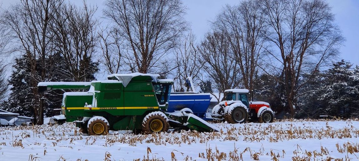 Tractor on field against sky during winter