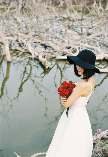 Woman in hat with bouquet standing against lake