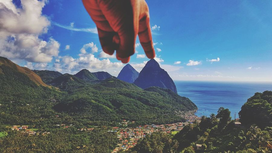 Optical illusion of cropped hand touching mountain peak by sea