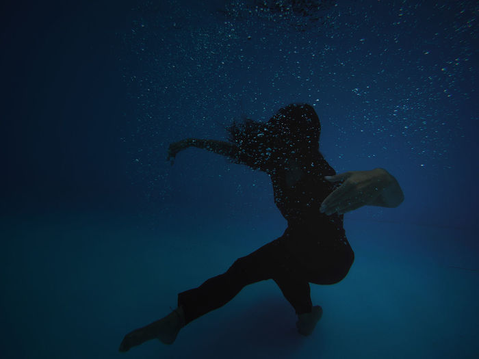 Young woman swimming underwater in pool