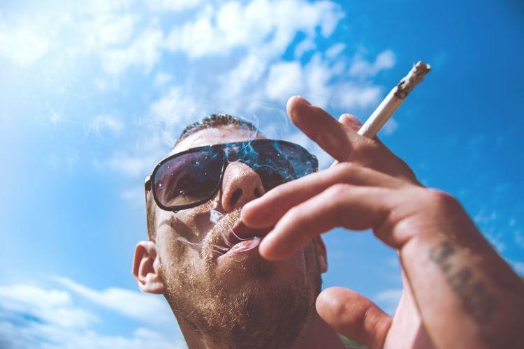 Man smoking against blue sky