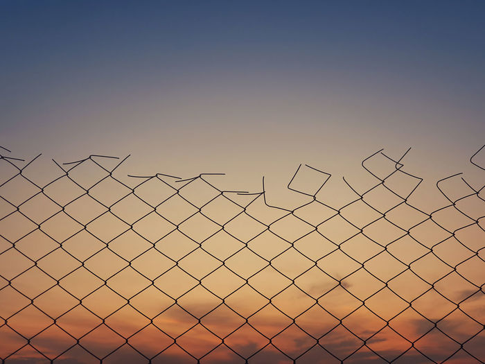 Low angle view of silhouette fence against clear sky during sunset