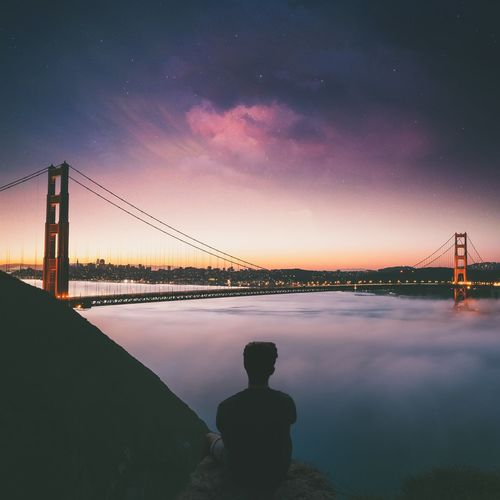 Rear view of man sitting against golden gate bridge during sunset