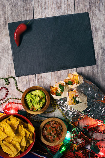 Mexican holiday Cinco De Mayo series with drinks, food, colorful lights and lots of fun. Chile Cinco De Mayo Cinco De Mayo! Holiday Sign Wood Backgrounds Blackboard  Blank Chile Peppers Copyspace Guacamole Mexican Overhead Overhead View Pepper Poster Background Table Taco