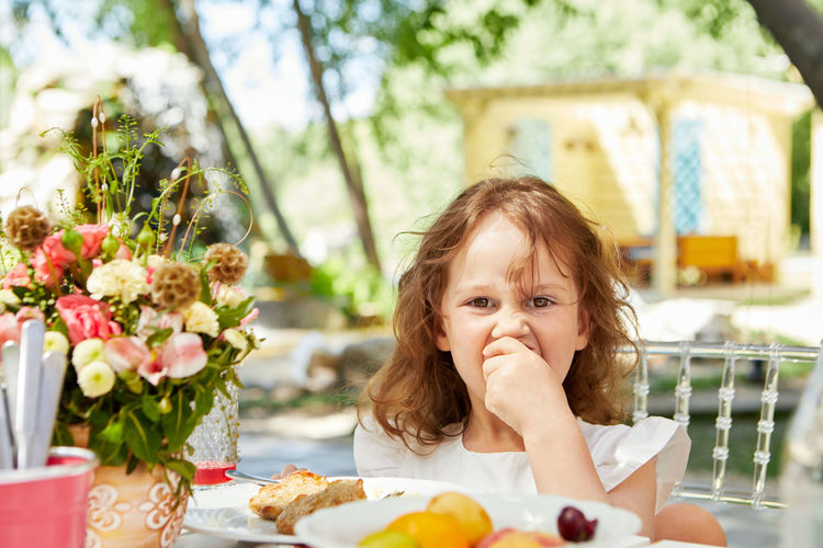 Portrait of girl eating food at cafe