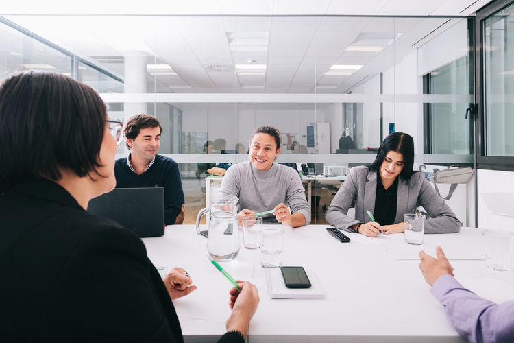 Business people sitting by table in conference room
