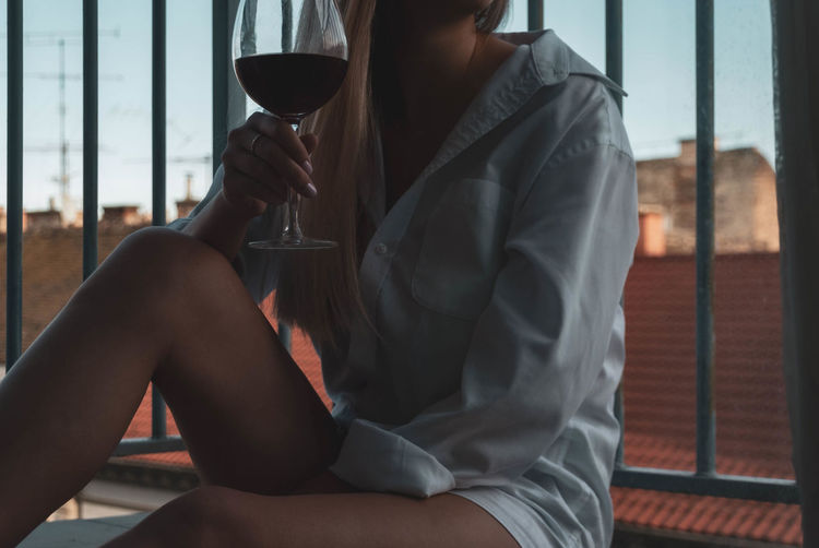 Midsection of woman holding wineglass while sitting against railing