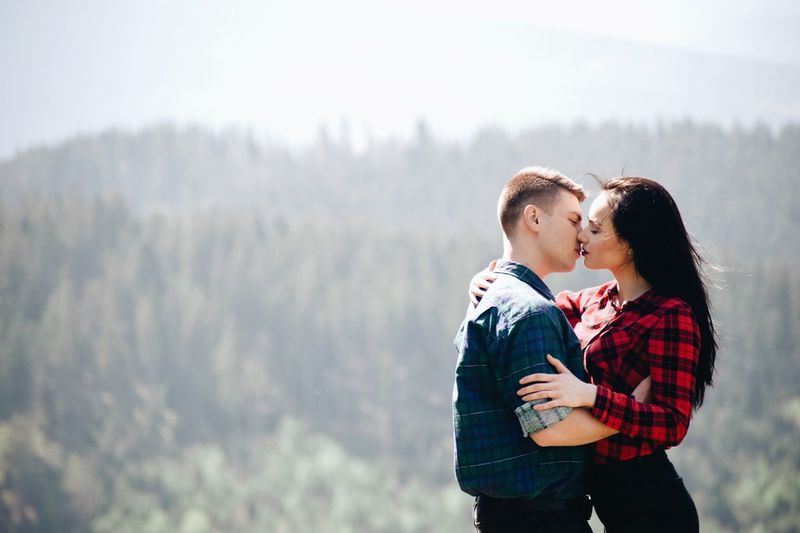 Side View Of Young Couple Kissing While Standing In Forest