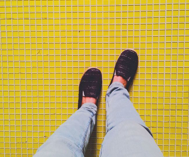 Low section of man standing on yellow tiled floor