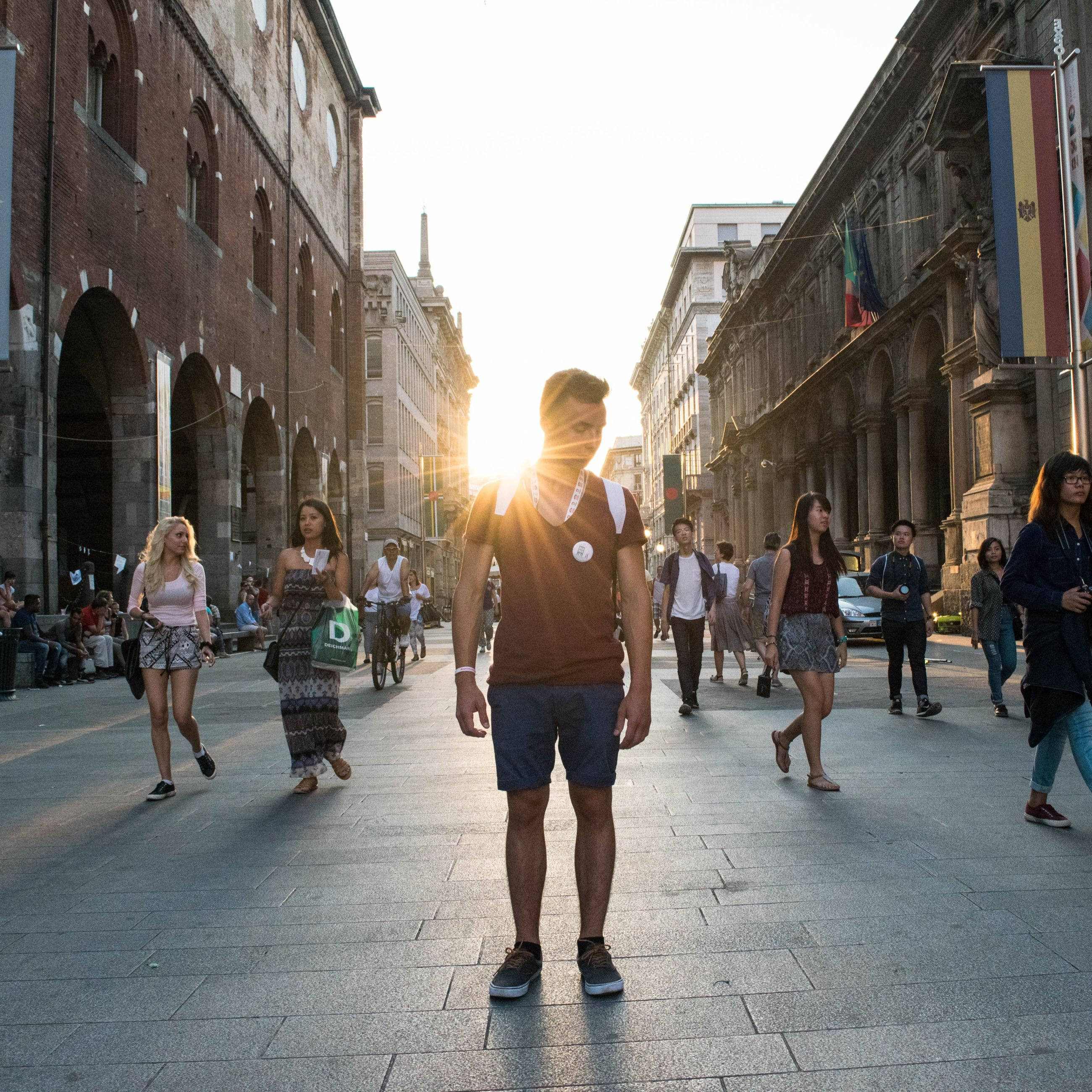 building exterior, architecture, built structure, lifestyles, men, large group of people, walking, city, full length, street, leisure activity, person, city life, sunlight, casual clothing, lens flare, sun, sunbeam, clear sky