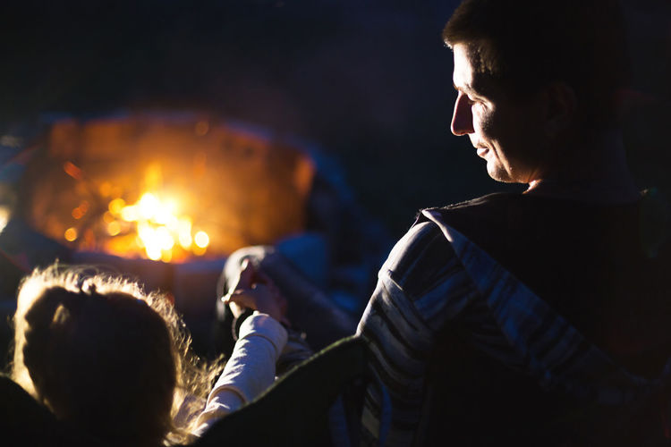 Dad and daughter sit at night by the fire in the open air in the summer in nature. family camping