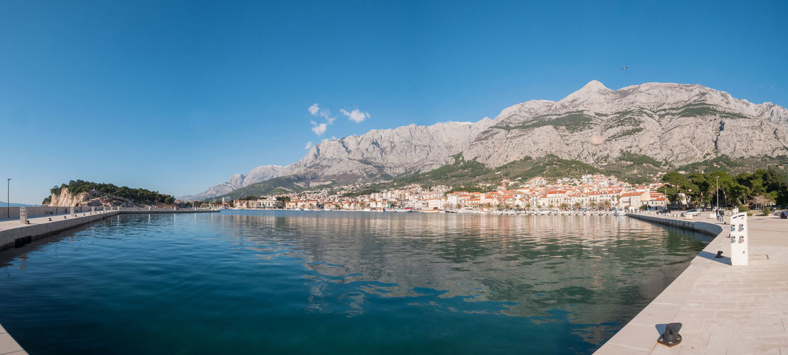 Panorama of city Makarska in Croatia on sunny day Water Mountain Sky Scenics - Nature Beauty In Nature Nature Day Mountain Range Tranquility Outdoors Tranquil Scene Panorama Landscape Sunny Summer Makarska Makarska Riviera Dalmatia Croatia Europe Adriatic Sea Mediterranean  City Town Travel Vacations Holiday Tourism Calm No People Nobody Empty Scenics Rest Blue Biokovo