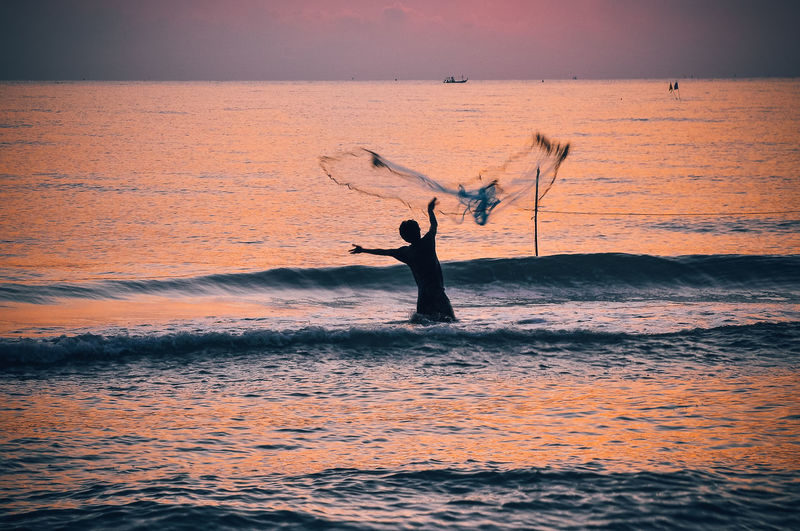 Rear view of man fishing in sea during sunset