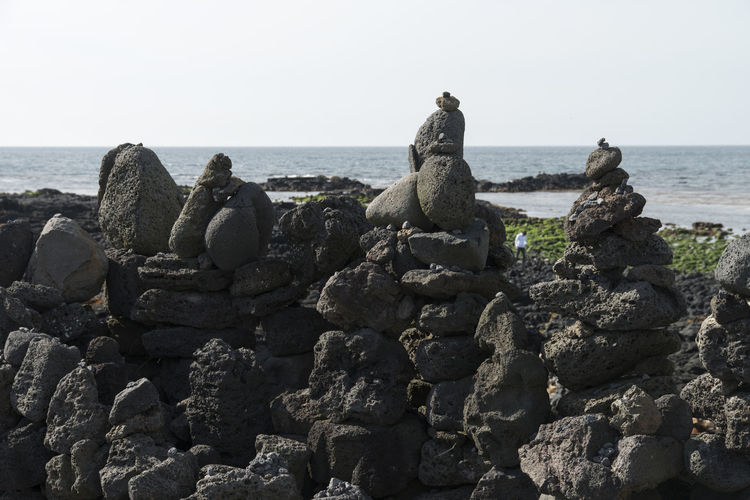 seaside view of stone stack at Gujwaup in Jeju Island, South Korea Beach Beauty In Nature Clear Sky Coastline Day Groyne Gujwaup Horizon Over Water JEJU ISLAND  Nature No People Outdoors Rock - Object Rock Beach Scenics Sculpture Sea Seaside Sky Stack Statue Stone Stack Tranquil Scene Tranquility Water