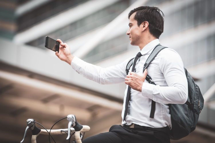 Man photographing with mobile phone in city