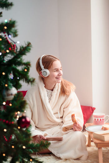 Young girl listening to Christmas carols through her headphones Celebrating Celebration Christmas Decorated Device Enjoying Fun Gift Girl Happy Headphones Holiday Home Joy Listening Mobile Music Person Phone Present Smart Smiling Tree Vertical Young