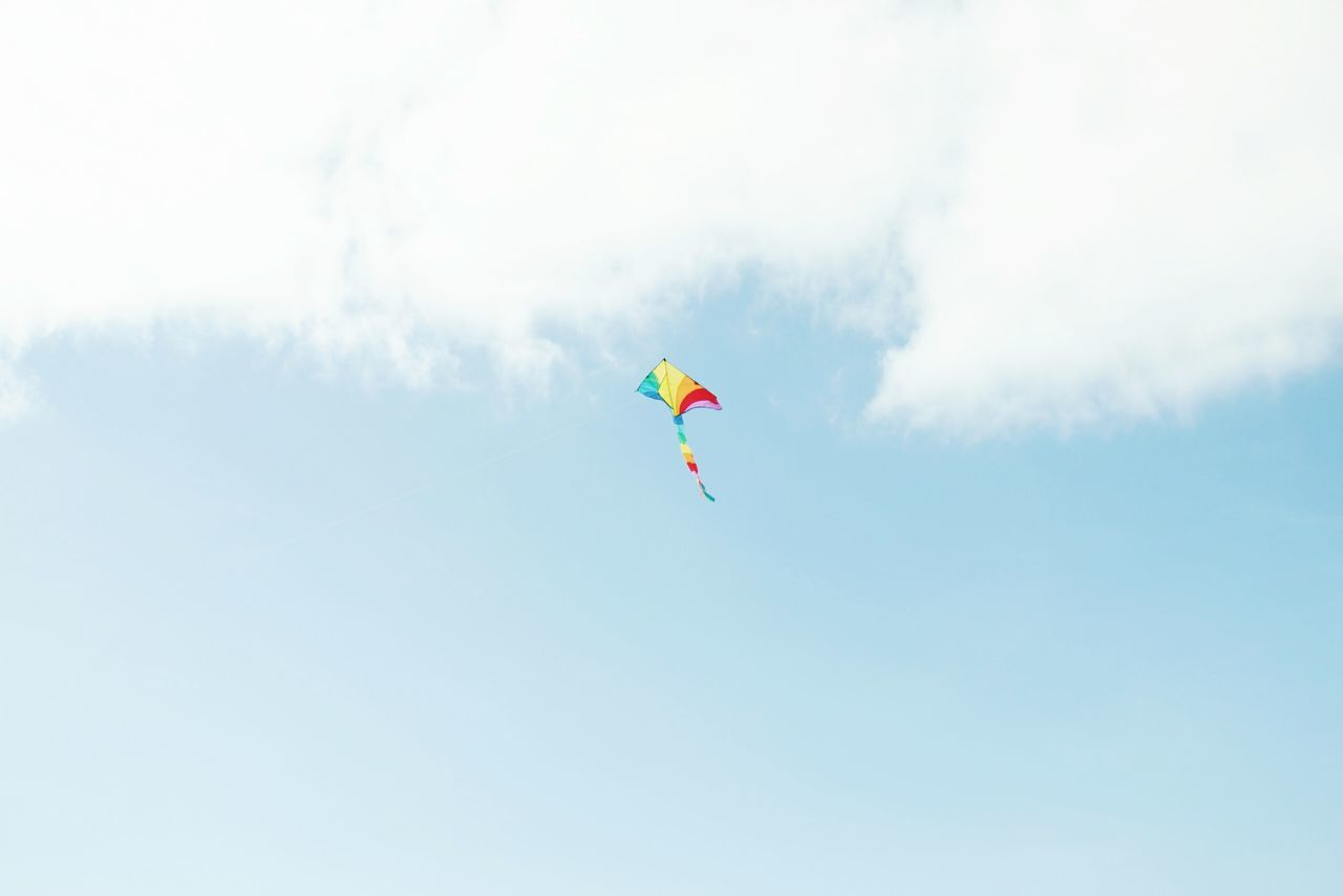 Low angle view of multi colored kite flying against cloudy sky