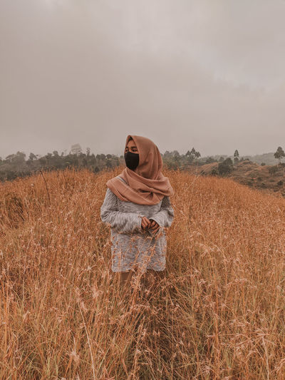Woman wearing mask standing on field against sky