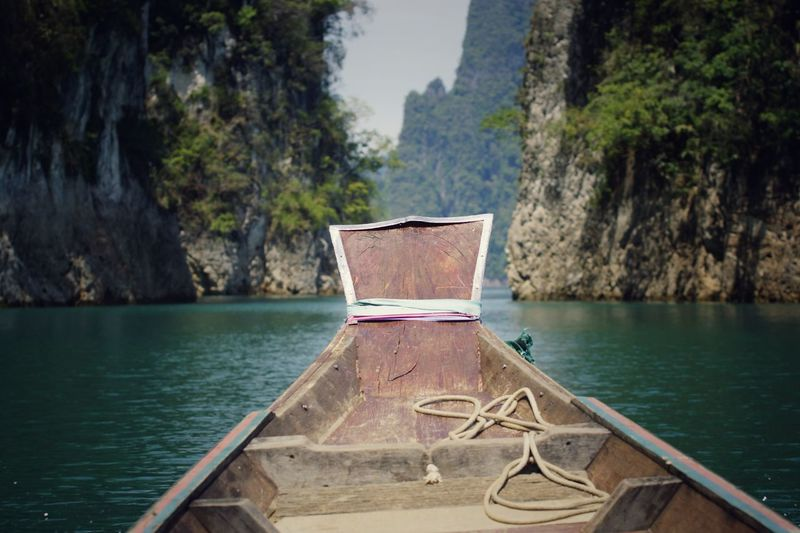 Longtail boat over river against rock formations