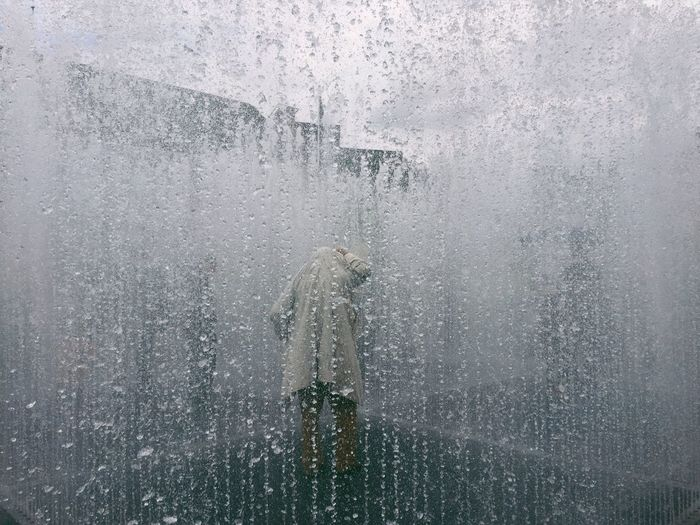 Person seen through glass window during monsoon