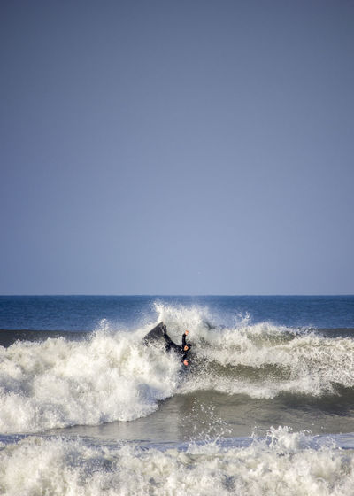 Surfer In Sea Against Clear Sky