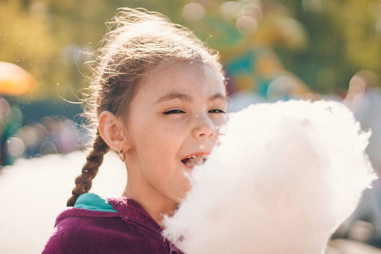 Close-up of cute girl eating cotton candy