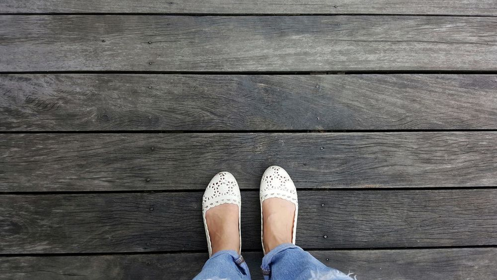 Low Section Human Leg Human Foot Standing Directly Above Human Body Part Wood - Material Day Outdoors One Person Style Wooden Floor Hardwood Floor Vintage Classic Retro Hipster Copy Space White Shoes One Woman Only Lifestyles Adult Selfies Textures And Surfaces Jeans Clothing