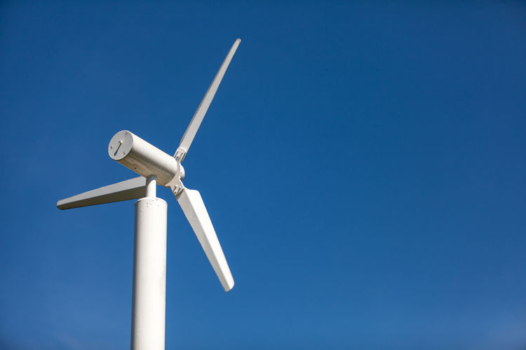 Low angle view of windmill against clear blue sky