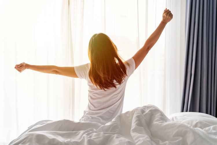 Rear view of woman with arms raised on bed