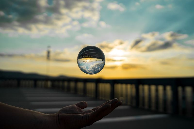 Cropped hand of man catching crystal ball against sky during sunset