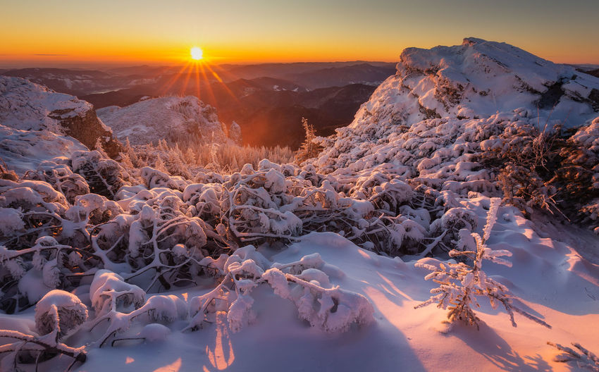 Scenic view of snowcapped mountains against sky during sunset in ceahlau mountains