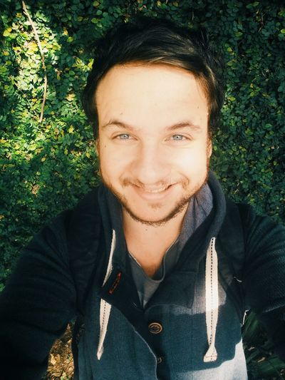 High angle portrait of man taking selfie while smiling against plants