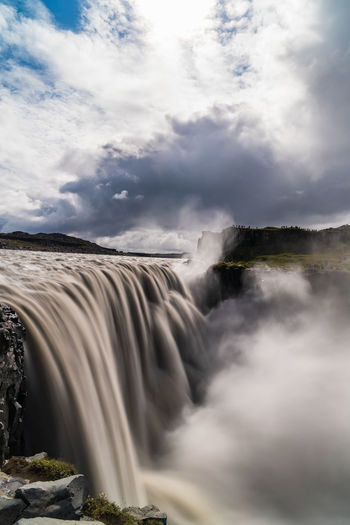 View of waterfall against cloudy sky - dettifoss