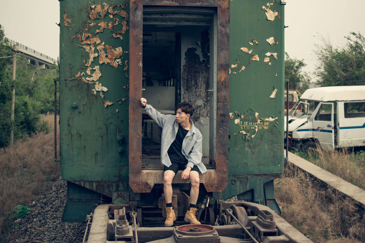 Full length of man sitting at railroad station