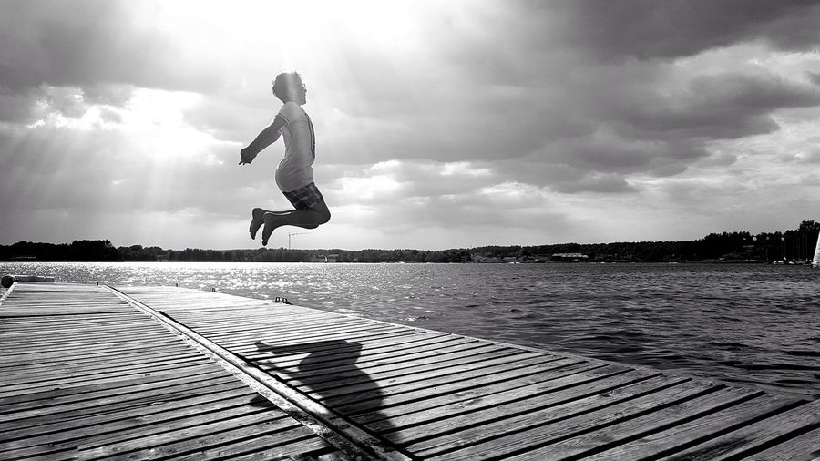 Boy Jumping On Pier Over Sea Against Sky