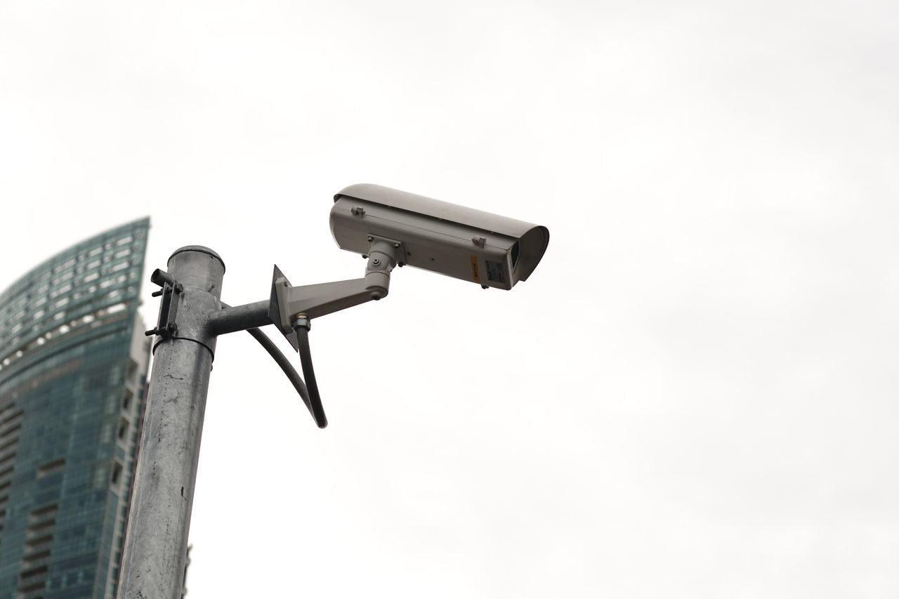 sky, security camera, clear sky, surveillance, security system, low angle view, security, technology, safety, protection, copy space, metal, no people, outdoors, day, nature, focus on foreground, control, camera - photographic equipment, photography themes, safety equipment, home video camera, electrical equipment