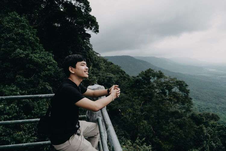 Side view of man sitting on mountain against sky