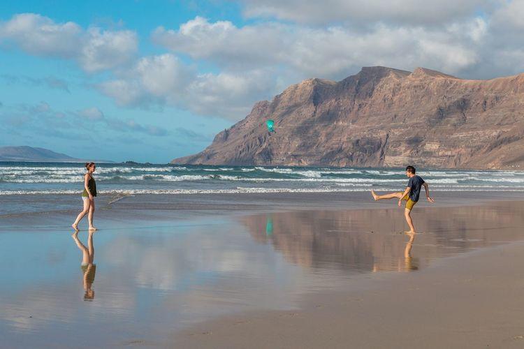 People walking on beach against sky
