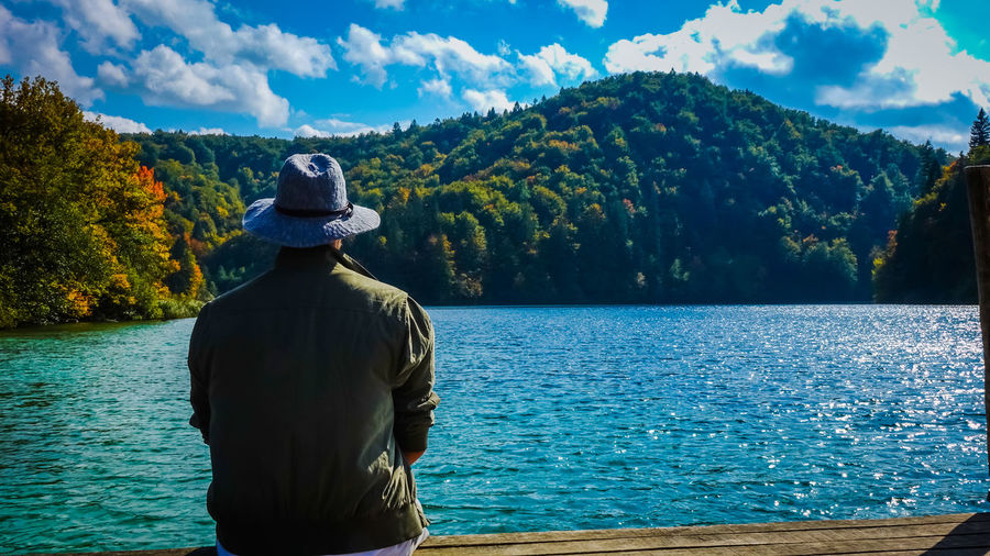 Rear view of man looking at lake while sitting on pier against sky